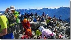 2-23剱岳山頂、多くの登山者でにぎわっています。後方は鹿島槍ケ岳などの後立山連峰